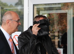 Novak Buha se krije od fotoreportera ispred Palate pravde